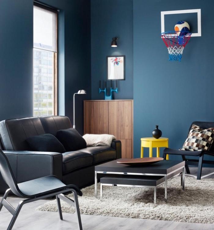 la luminosité de la peinture bleu canard des murs est mise en valeur par les touches de gris anthracite et les accents colorés