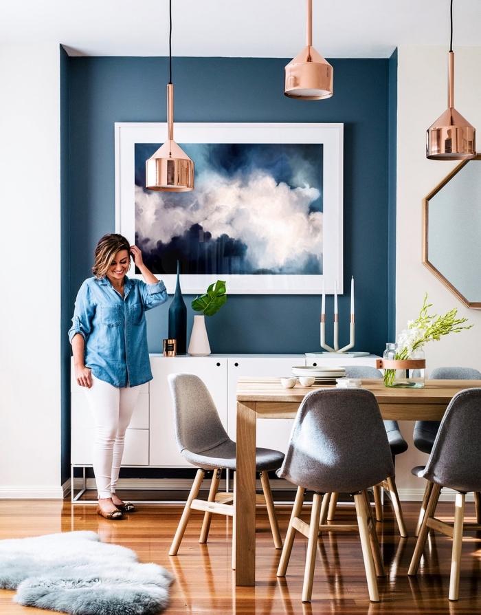 coin de mur peint en bleu marine couleur qui structure l'espace du salon scandinave, salon bleu et blanc aux accents cuivre et bois blond