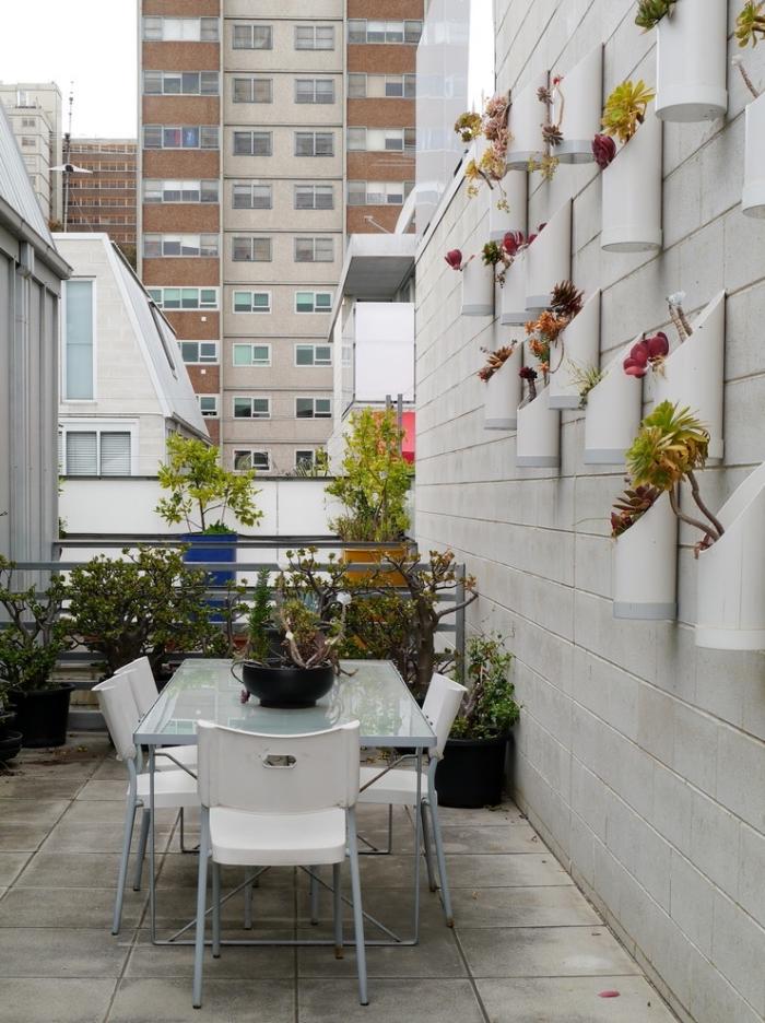 des pots originaux avec des plantes exotiques, fixés au mur qui constituent un mur vegetal exterieur original en joli contraste avec les murs en ciment et le carrelage du balcon