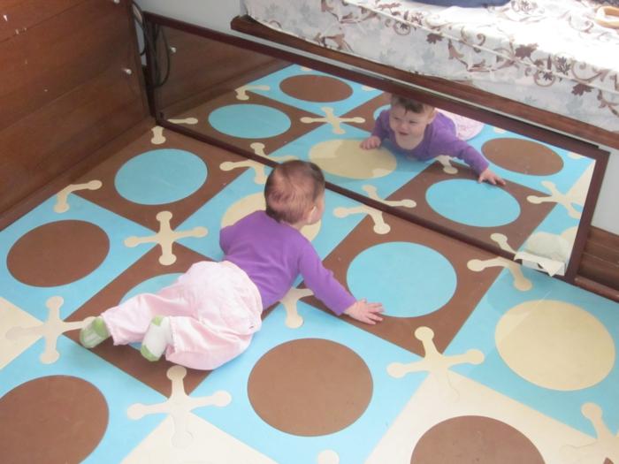 miroir montessori, lit montessori, sol recouvert de tapis ludique aux motifs cercles et croix en marron et bleu pastel, bébé qui se contemple dans le miroir