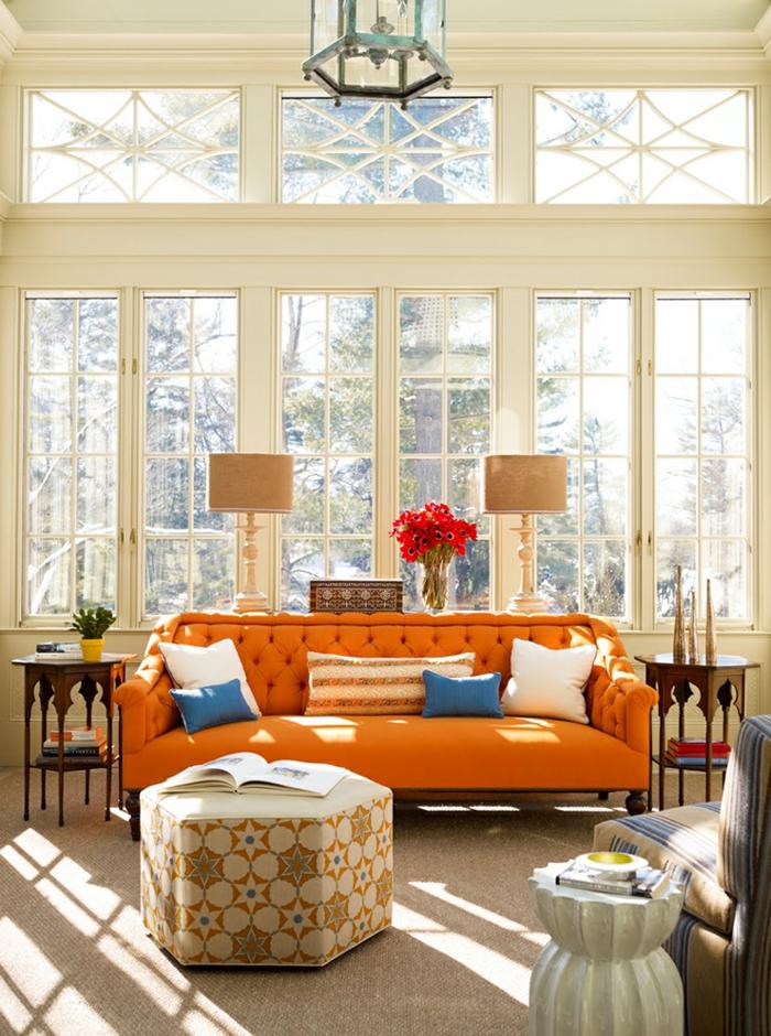 sofa orange capitonné, pouf beige, lampes de tables beiges, grande fenêtre, plafonnier lanterne