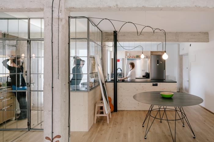 aménager un espace industriel, sol en bois, table ronde noire style industriel, murs en béton