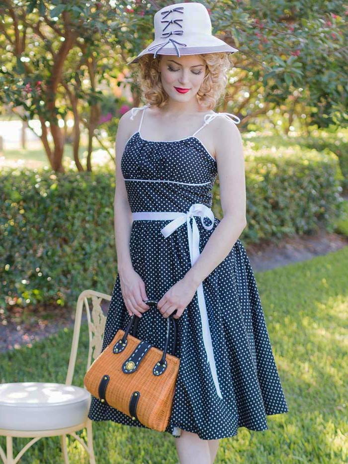 robe pointillée bleue, sac à main marron, ceinture blanche, canotier blanc