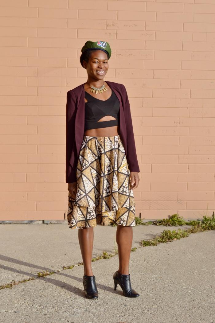 look urbain chic qui combine avec succès la mode militaire et le motif africain, une jupe midi évasée en imprimé wax assortie avec un crop top noir découpé