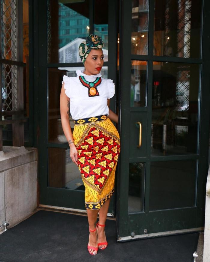 une jupe wax coupe crayons à motifs africains vitaminées combinée avec un top blanc à col et manches ruchés