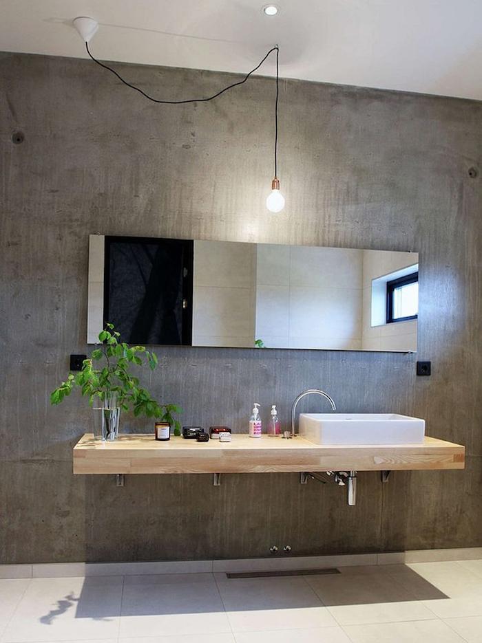 mur en béton ciré brut pour déco style industrielle avec meuble lavabo en bois suspendu et sol en carrelage