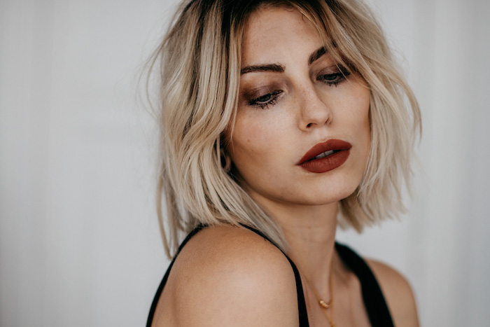 carré plongeant visage rond avec des racines foncées et longueurs blondes, maquillage femme foncé