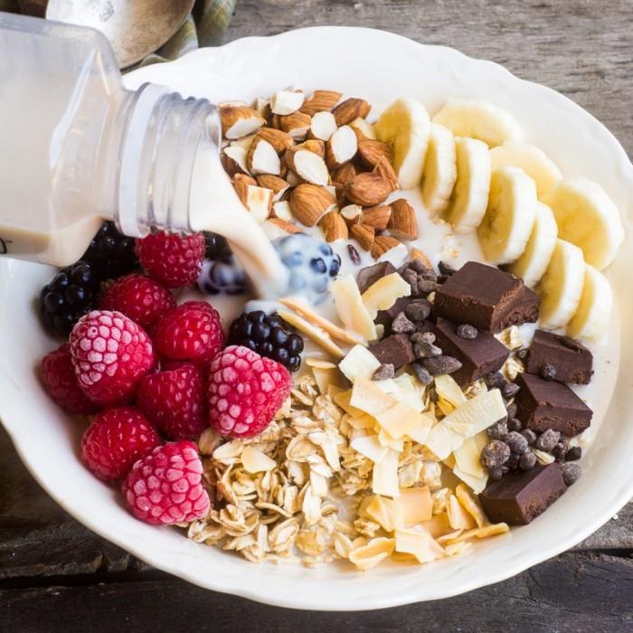 petit déjeuner régome flacons d avoine, chocolat, lait d amande, bananes, fruits rouges et amandes, coco râpé