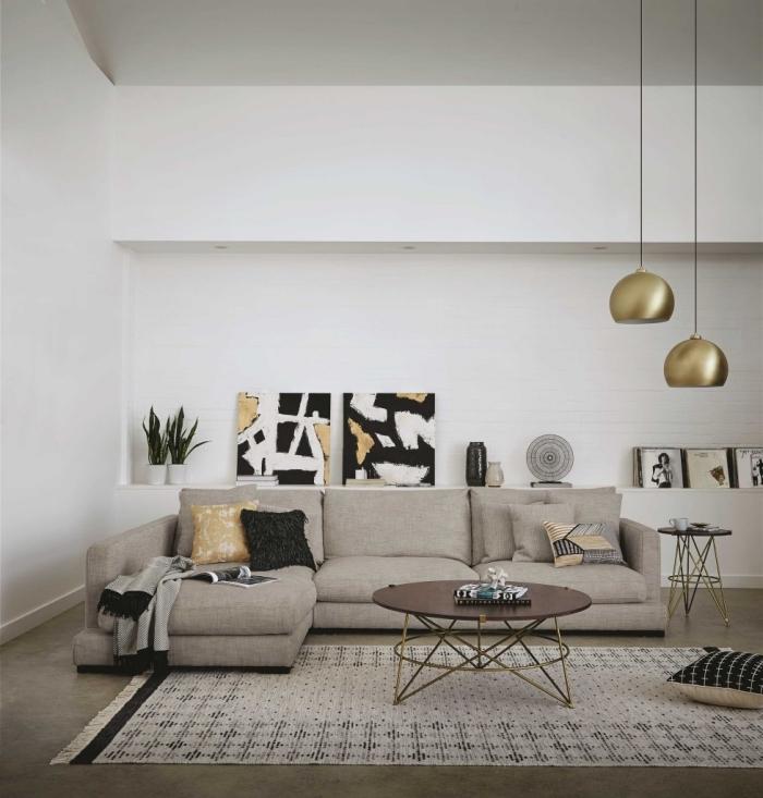 modèle de salon moderne aux murs blancs aménagé avec canapé d'angle et accessoires en finitions or et motifs ethniques