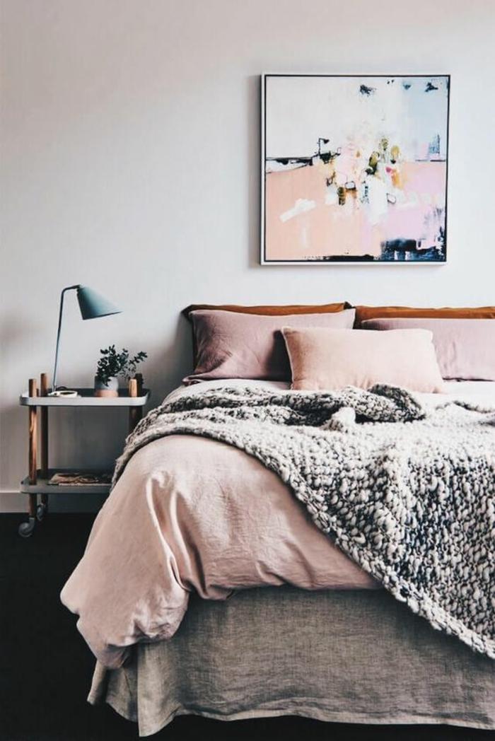 couverture vieux rose dans une chambre d'adulte, tableau art abstrait au-dessus du lit, couverture en grosse maille grise, coussins en couleur rose pale