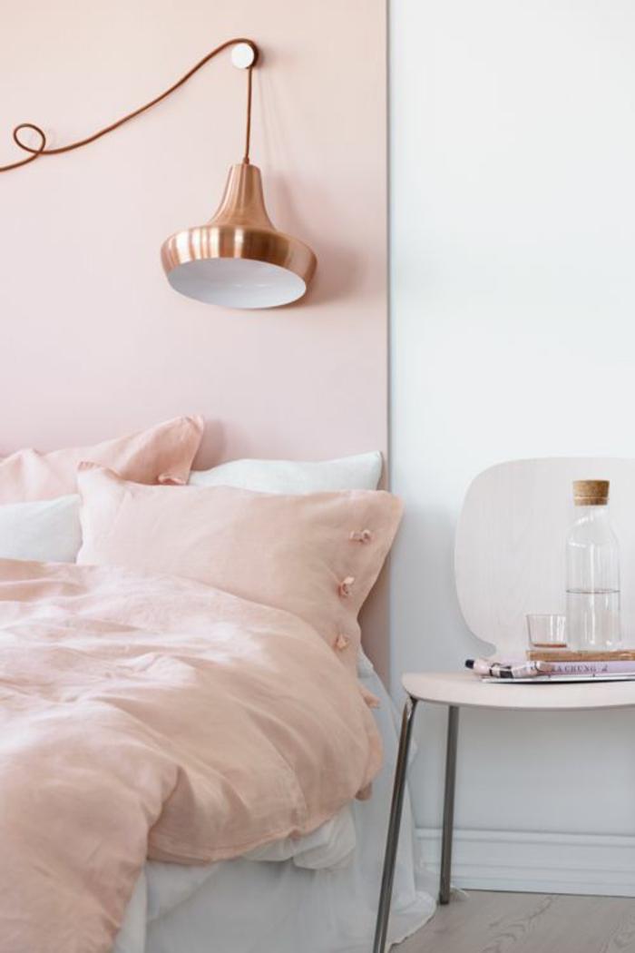 tete de lit en rose poudree, linge de lit couverture et coussins en couleur rose pale, luminaire en couleur or rose, chaise en plastique blanche avec des pieds en métal clair