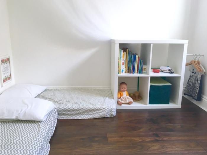 ambiance aux murs blancs, meuble casier de rangement blanc, cabane enfant lit, miroir montessori, meuble montessori, poupée et livres