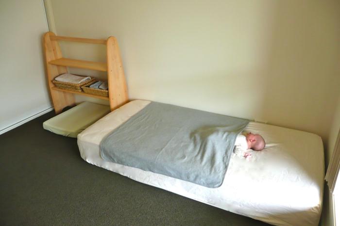miroir montessori, meuble de rangement en bois clair, murs en vert réséda, bébé qui dort, meuble montessori, couverture en vert réséda