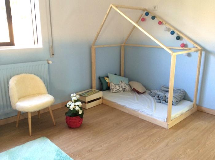 cabane enfant lit en bois clair, chambre montessori, mur bicolore en bleu pastel et blanc, guirlande de pompons colorés sur le sommet de la cabane lit