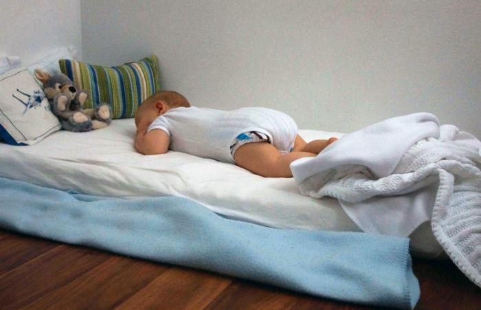 chambre montessori, lit bébé sans barreau, petit qui dort, animal en peluche grise, coussins multicolores, meuble montessori