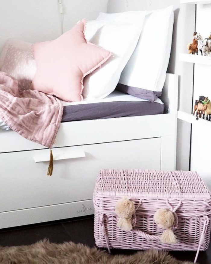 chambre avec lit en bois peint en blanc, coussin en couleur rose pale en forme d'étoile, deux coussins blancs, malle en rotin tressé peinte en rose avec deux pompons décoratifs devant