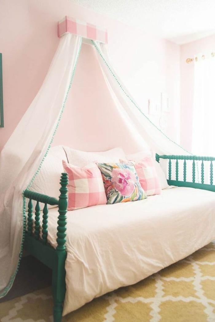 chambre adolescent avec grande moustiquaire en tissu couleur rose pale, tapis moutarde aux losanges blancs, lit avec des barreaux en bois peint en vert aux deux extremités