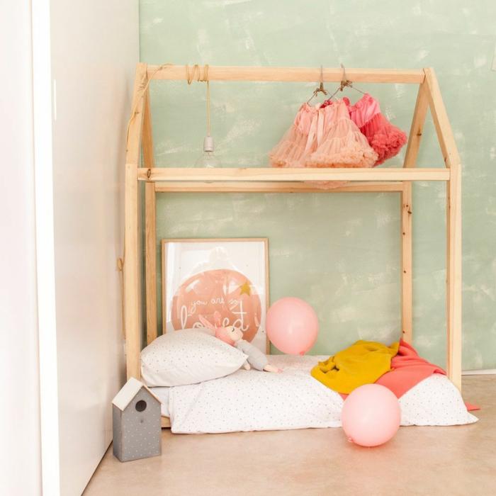 chambre montessori aux murs vert d'eau, lit cabane montessori en bois clair, lit montessori installé dans un angle, sol recouvert de parquet PVC beige clair