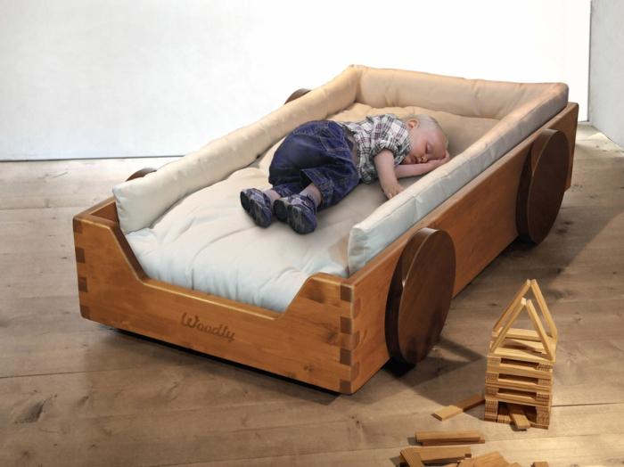 chambre enfantine avec lit bébé sans barreau, matelas blanc crème, lit en forme de voiture en bois marron avec quatre roues, parquet en bois gris, jouet de construction en bois