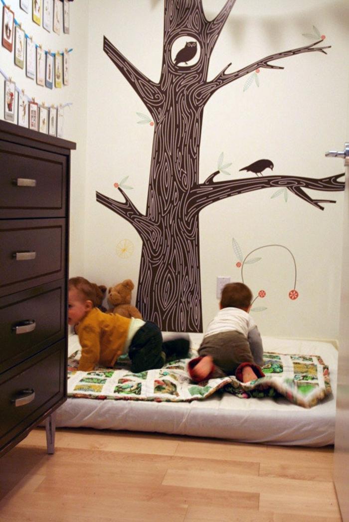 murs chambre d'enfant en couleur blanc crème, grand arbre en marron peint avec une chouette et un corbeau sur ses branches, lit bébé sans barreau