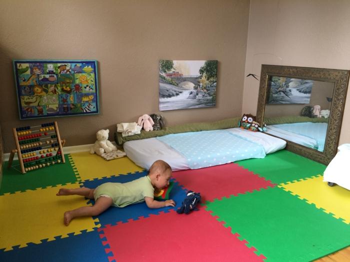 meuble montessori, miroir montessori, chambre de bébé en couleurs vives, revetement du sol en morceaux de puzzle, murs en marron clair, tableau avec chute d'eau et paysage nature, panneau haut en couleurs
