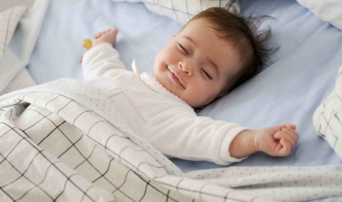 bébé qui dort heureux dans son lit, lit bébé sans barreau, linge en bleu pastel et blanc avec des carreaux taupe, petit souriant dans son lit