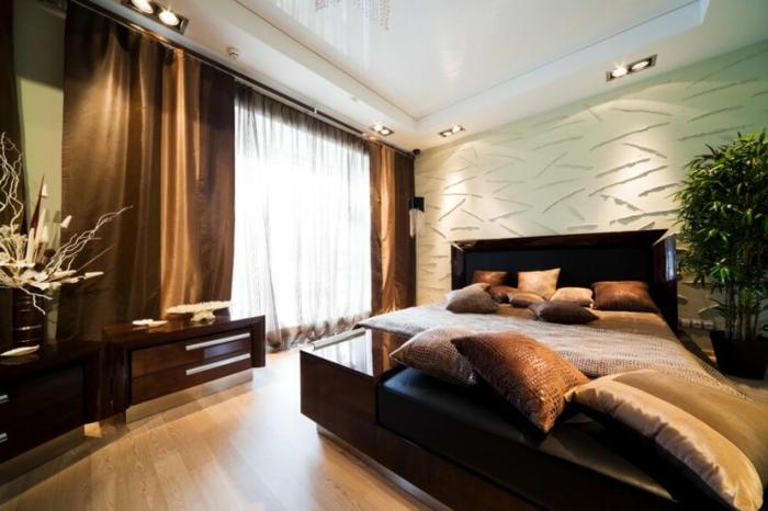 chambre moderne avec lit wengé, plusieurs coussins déco, rideaux marron, faux plafond éclairé
