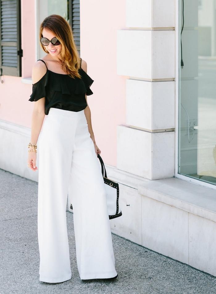 modèle de pantalon fluide femme blanc porté avec top noir à bretelles et épaules dénudées, coloration balayage blond