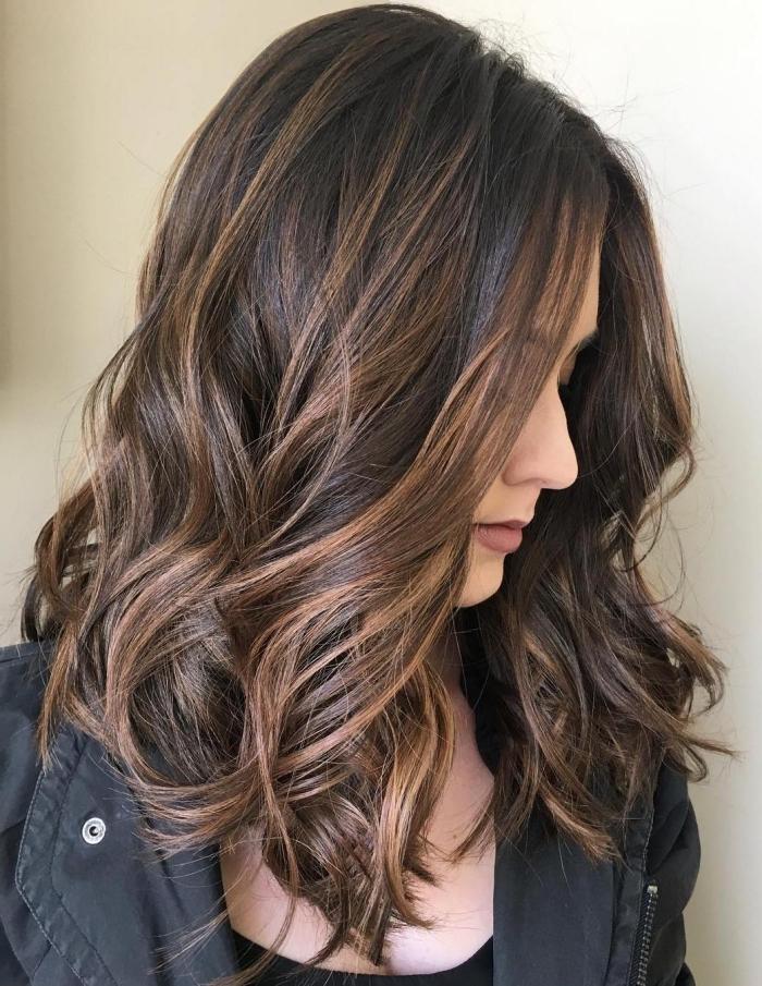 exemple de balayage sur cheveux brun, coupe de cheveux longs et ondulés de couleur marron avec mèches cuivrées