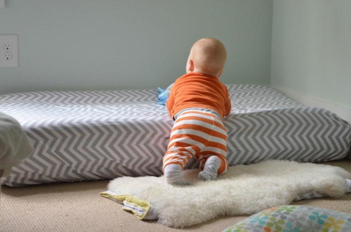 chambre montessori, matelas aux rayures diagonales blanches et taupe, murs réséda, moquette beige, bébé qui grimpe sur son lit sans barreaux