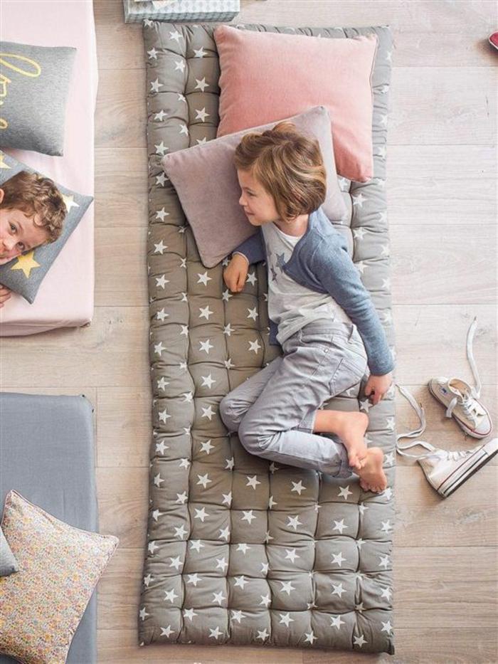 chambre montessori, lit bébé sans barreau, meuble montessori, matelas gris perle en couleur taupe avec des étoiles blanches, coussins rose poudré et lila en peluche