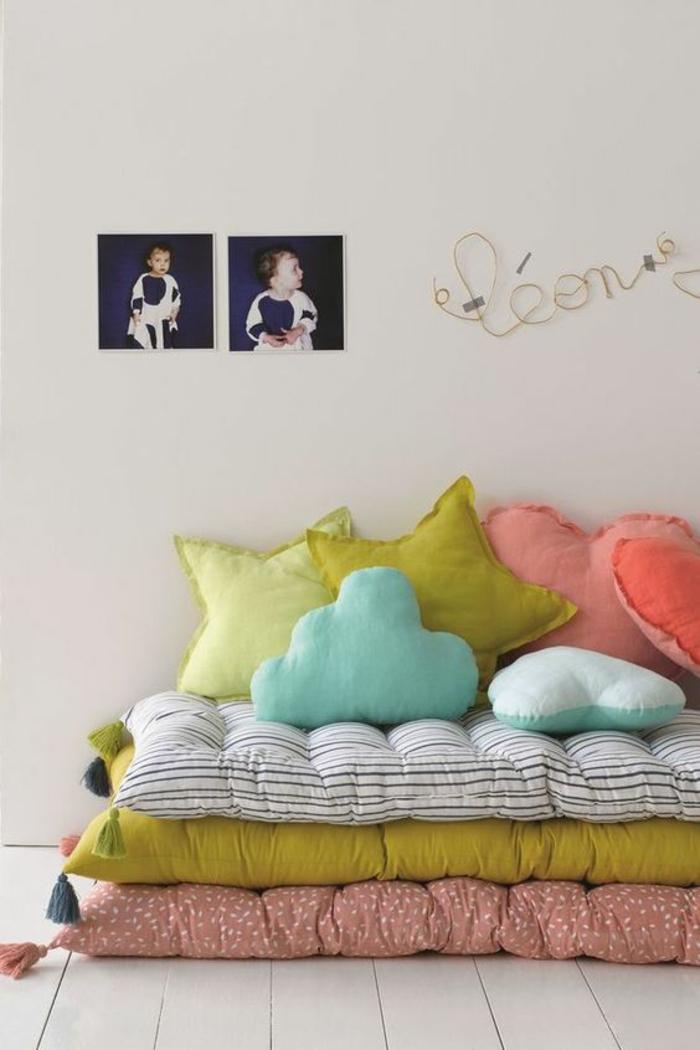lit montessori, chambre montessori, meuble montessori, trois matelas colorés posés l'un sur l'autre, lit bébé sans barreau, murs beiges, coussins en rose et réséda en forme d'étoiles