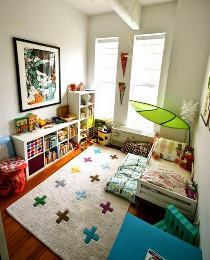 chambre montessori, tapis rectangulaire blanc crème avec des motifs mathématiques plus, murs vert menthe, grand tableau en couleurs représentant un visage d'enfant, meuble de rangement blanc modulaire