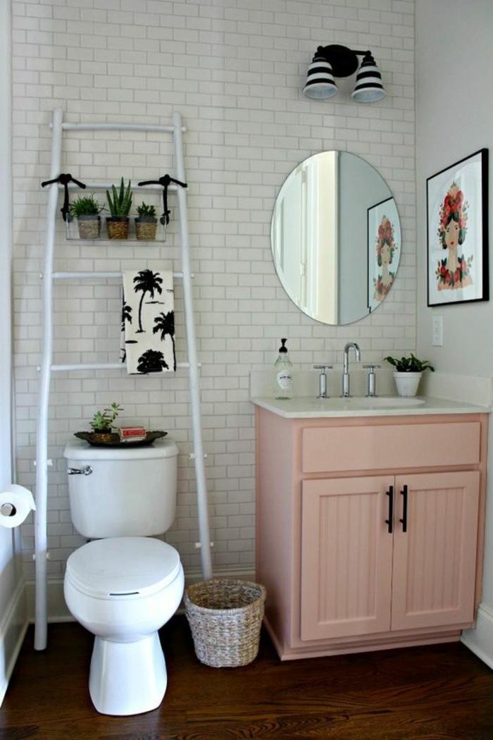 salle de bains rose poudree, carrelage mural blanc aux motifs briques blanches, tableau mural avec portrait de femme hyper coloré, meuble en couleur rose poudré