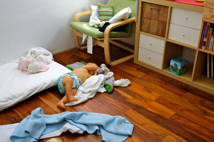 meuble montessori, bébé couché a cote hors du lit, chambre montessori, lit montessori,parquet encastrable en nuances marrons, meuble de rangement beige et blanc