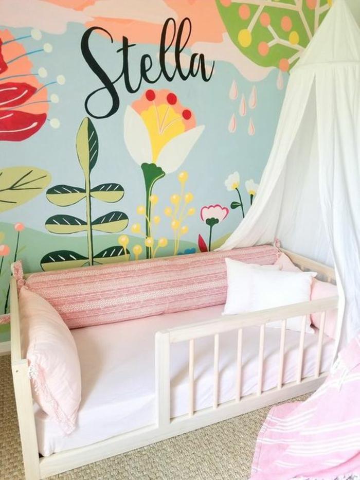 murs dessinés en couleurs pastels avec des motifs foret, plantes, fleurs et soleil, inscription nom de la fillette Stella, lit Montessori avec barreaux partiels, moquette beige, moustiquaire en tissu blanc et rose