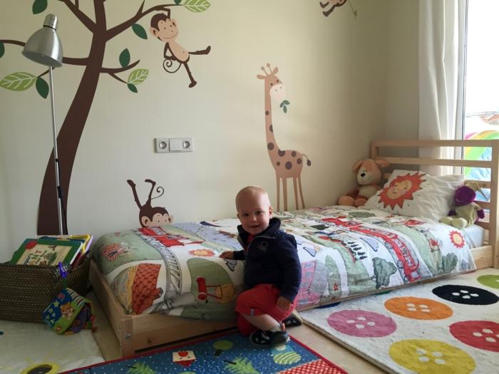 lit bébé sans barreau, murs en jaune pastel, tapis blanc crème avec des grands boutons en couleurs vives, arbre marron avec un petit singe souriant grimpant aux branches