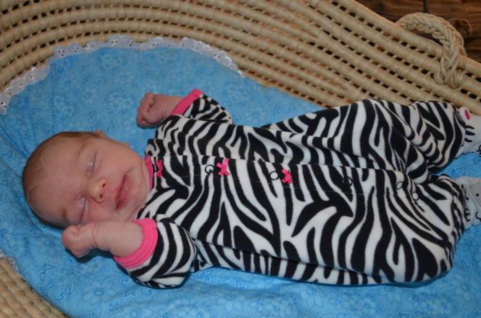 bébé qui dort dans son berceau en rotin tressé, chambre montessori, petit avec pyjama aux prints zèbre, lit bébé sans barreau
