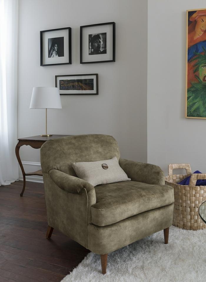 grand fauteuil en velours vert olive, petit coussin rectangulaire avec logo, salon classique, trois petits tableaux aux cadres noirs et un grand tableau au cadre doré, meuble relooké