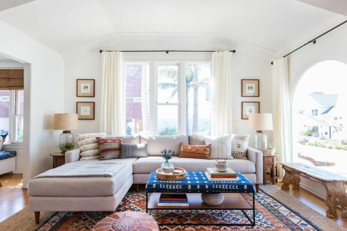 renover meuble bois, canapé d'angle en tissu gris clair, petite table basse carrée avec couverture en bleu et blanc, salon avec plafond avec un arc léger