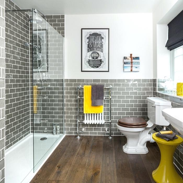 exemple salle de bain gris et blanc avec carrelage design briques grises et plancher bois foncé, déco avec accessoires jaune