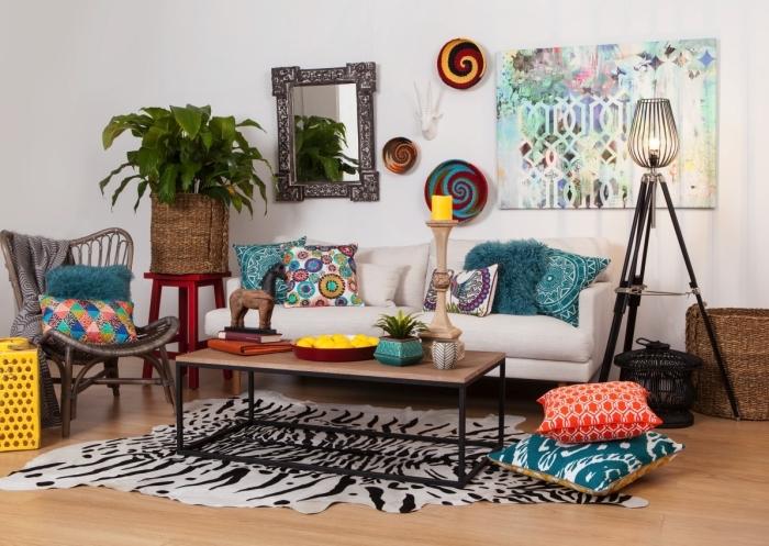 aménagement de pièce en style ethnique avec poterie pour déco murale et coussins aux motifs colorés, modèle de chaise papillon avec plaid gris