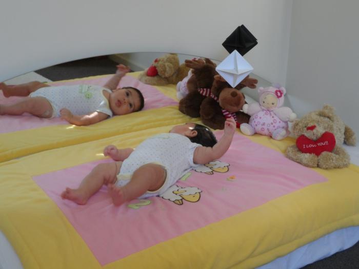 bébé couché sur un lit bébé sans barreau, couverture jaune et rose, animaux en peluche, objets en carton coloré suspendu au-dessus de bébé
