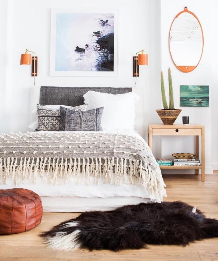 aménagement de chambre à coucher en style bohème avec lit en tête grise couvert de plaid gris à franges et coussins gris