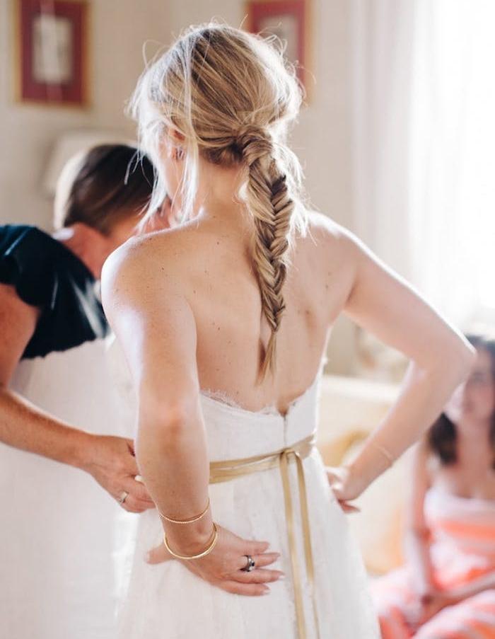 tresse épi en arrière de la tête avec des mèches libres rebelles, robe de mariée simple, ruban or