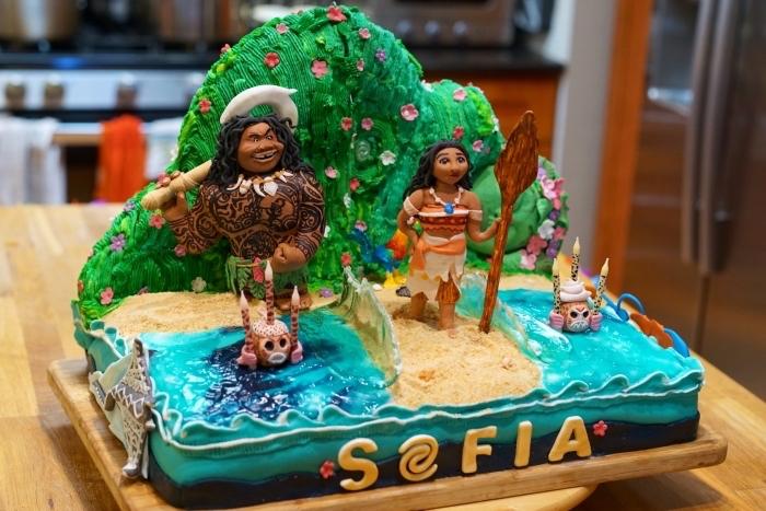 jolie idée pour un gâteau d'anniversaire enfant sur le thème Vaiana avec figurines des personnages et à design nature et océan