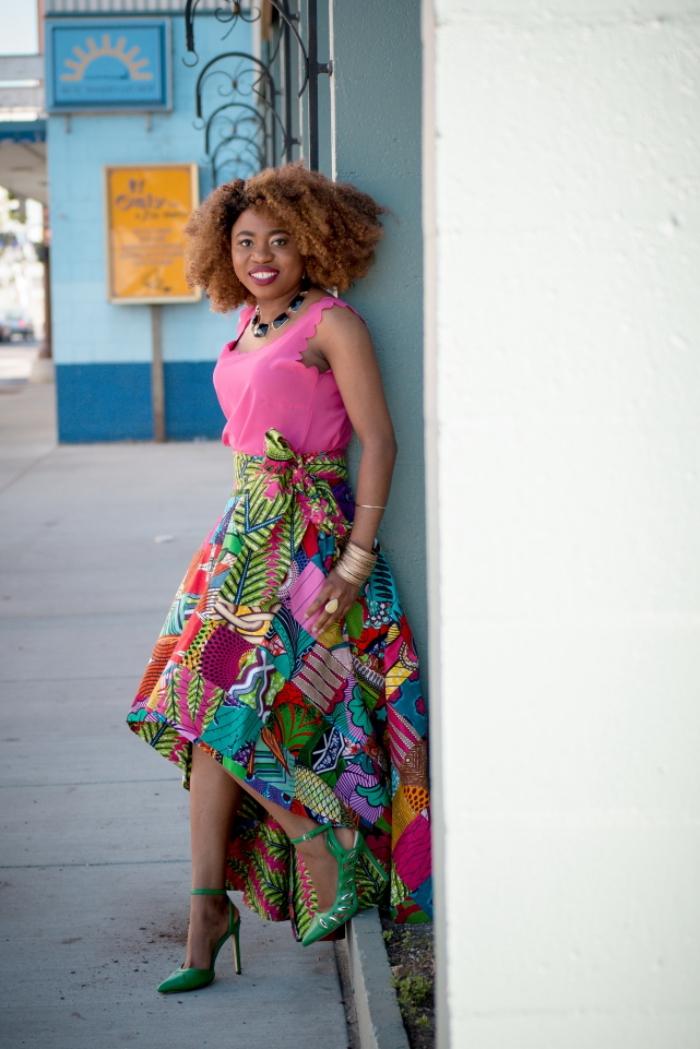 look frais idéal pour l'été en jupe wax asymétrique à motifs patchwork bariolés assortie avec un débardeur rose et des sandales à talons hauts verts