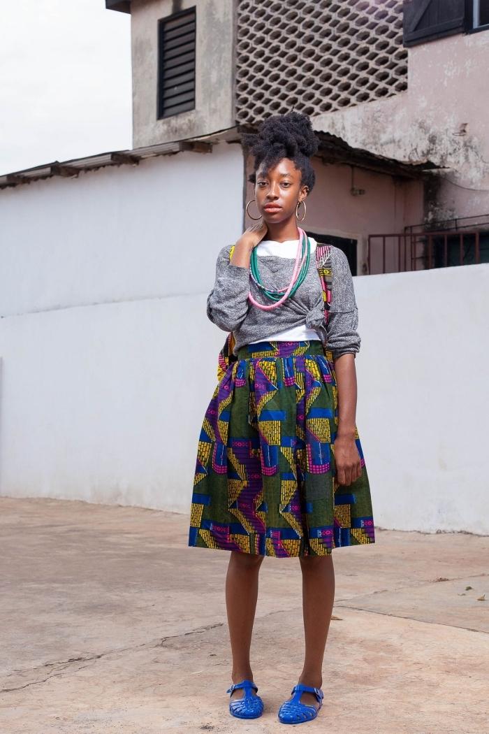une jupe midi en tissu wax à motifs géométriques en vert, bleu, jaune et rose, assortie avec un pull gris noué pour un look moderne et frais