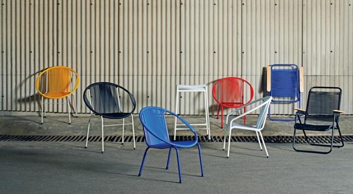 customiser meuble, fauteuils bas en métal coloré, murs revêtus de métal couleur crème, huit fauteuils en couleurs vibrantes, rouge et bleu roi, blanc, jaune, noir et blanc