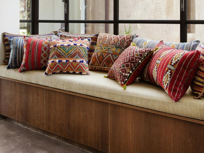 renover meuble bois avec des coussins en style ethnique, multitude de coussins qui couvrent un banc sur la longueur d'une fenêtre large